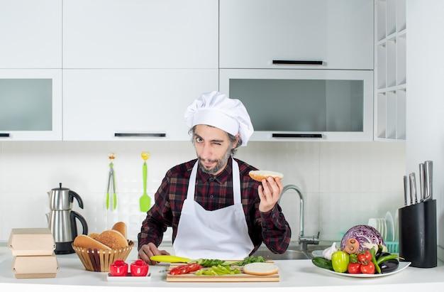 Vue de face du chef masculin cligne des yeux tenant du pain hamburger dans la cuisine
