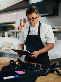 Vue de face du chef masculin contrôle le presse-papiers dans la cuisine