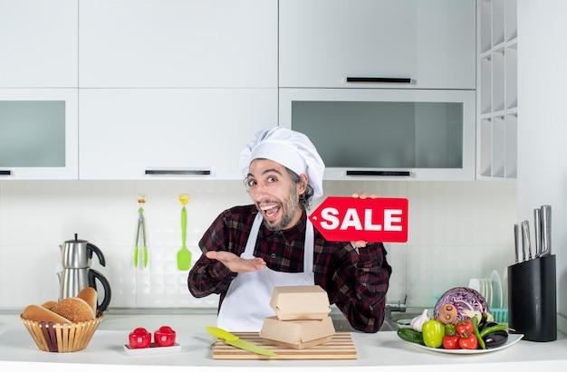 Vue de face du chef masculin demandé en uniforme brandissant un panneau de vente rouge dans une cuisine moderne