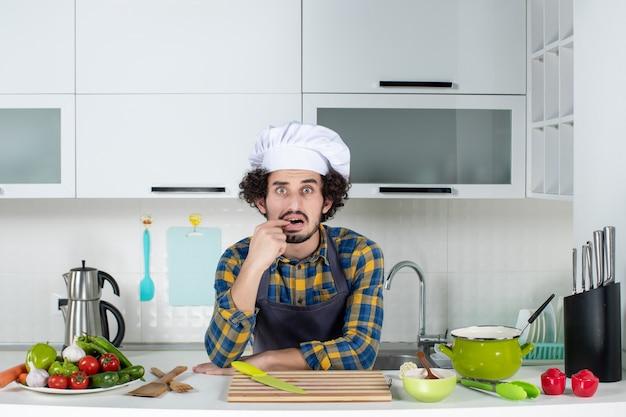 Vue de face du chef masculin avec des légumes frais se sentant confus dans la cuisine blanche