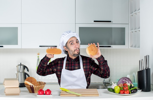 Vue de face du chef masculin perplexe tenant du pain à deux mains dans la cuisine