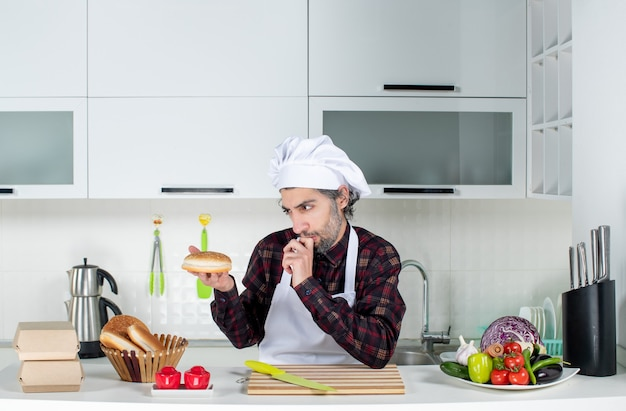 Vue de face du chef masculin réfléchi regardant le pain dans la cuisine