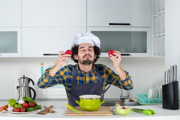 Vue de face du chef masculin rêveur avec des légumes frais tenant des poivrons rouges dans la cuisine blanche