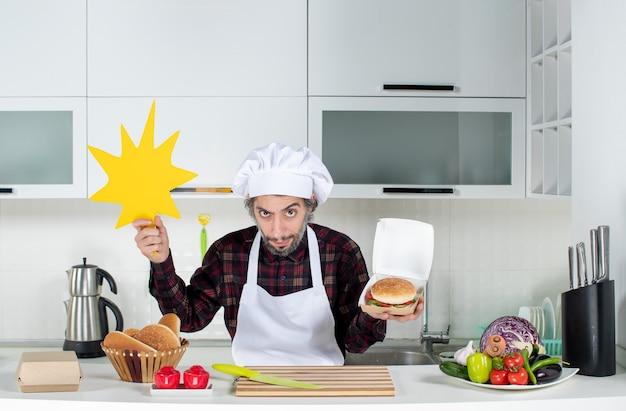 Vue de face du chef masculin sceptique brandissant un panneau de crunch de boom et un hamburger dans une cuisine moderne