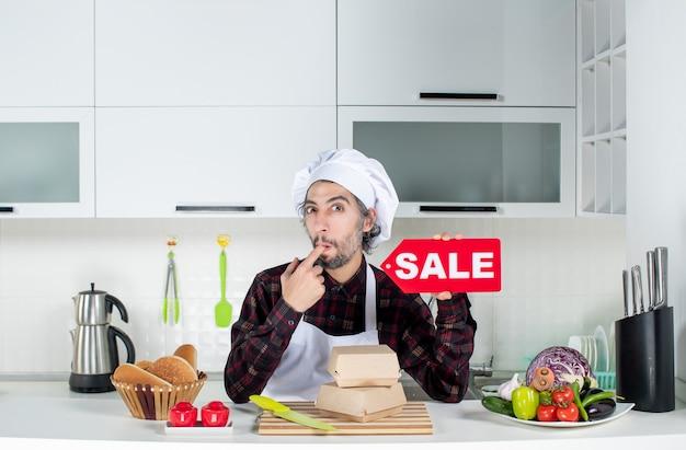Vue De Face Du Chef Masculin Sceptique En Uniforme Brandissant Un Panneau De Vente Rouge Mettant Le Doigt Dans Sa Bouche Dans Une Cuisine Moderne Photo gratuit