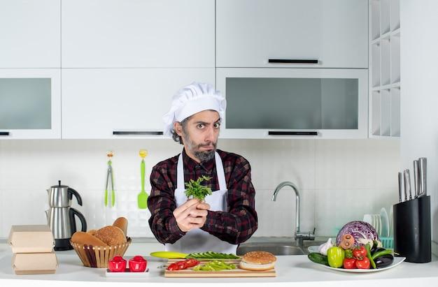 Vue de face du chef masculin sérieux tenant des verts dans la cuisine