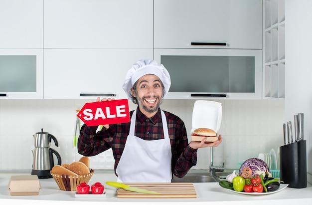 Vue de face du chef masculin souriant brandissant une pancarte de vente et un hamburger dans la cuisine