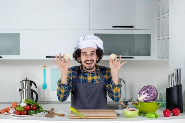 Vue de face du chef masculin souriant avec des légumes frais et cuisine avec des ustensiles de cuisine et tenant la nourriture dans la cuisine blanche