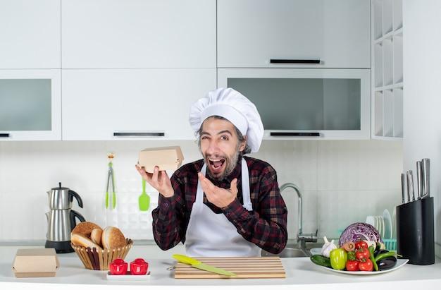 Vue de face du chef masculin en tablier tenant une boîte dans la cuisine