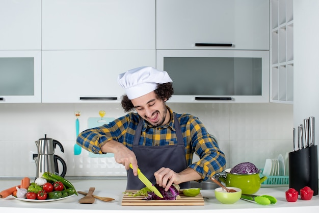 Vue de face du chef souriant et heureux avec des légumes frais coupant des aliments dans la cuisine blanche