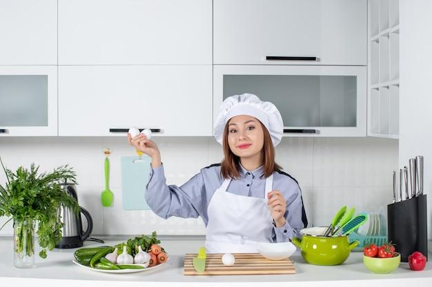 Vue de face du chef souriant et des légumes frais avec du matériel de cuisine et tenant des œufs dans la cuisine blanche