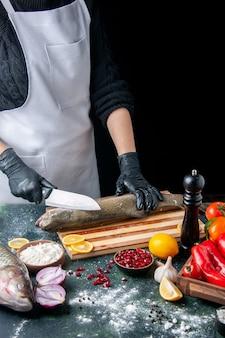 Vue de face du chef en tablier hacher le poisson cru sur planche de bois moulin à poivre bol de farine graines de grenade dans un bol sur la table de la cuisine