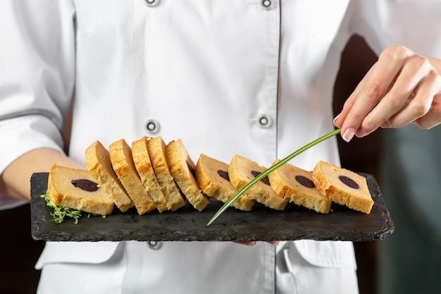 Vue de face du chef tenant une assiette de nourriture délicieuse