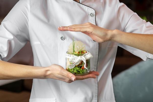 Vue de face du chef tenant une cuisine délicieuse