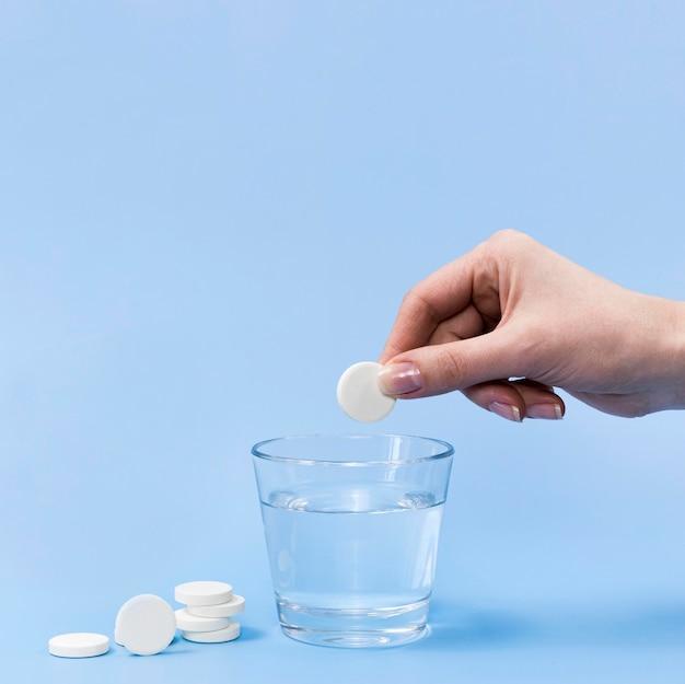 Vue de face du comprimé effervescent tombant à la main dans un verre d'eau