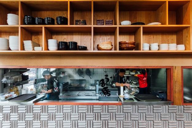 Vue de face du comptoir de cuisine ramen avec une étagère en bois sur le dessus.