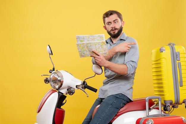 Vue de face du concept de voyage avec confus jeune homme assis sur la moto avec des valises sur elle pointant vers l'arrière tenant la carte sur jaune