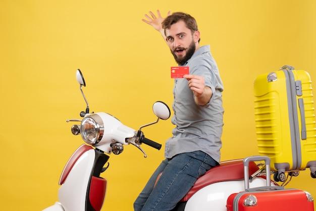 Vue de face du concept de voyage avec fier jeune homme ambitieux assis sur une moto avec des valises tenant une carte bancaire sur elle sur jaune