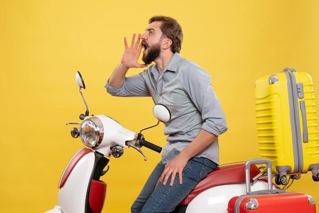 Vue de face du concept de voyage avec jeune homme assis sur une moto avec des valises sur elle appelant quelqu'un sur jaune