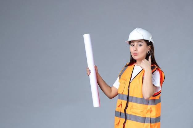 Vue de face du constructeur féminin avec une affiche dans ses mains sur un mur gris