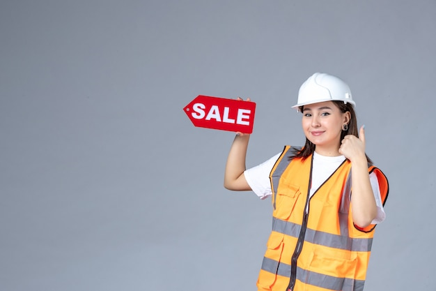 Vue de face du constructeur féminin tenant un tableau de vente rouge sur un mur gris