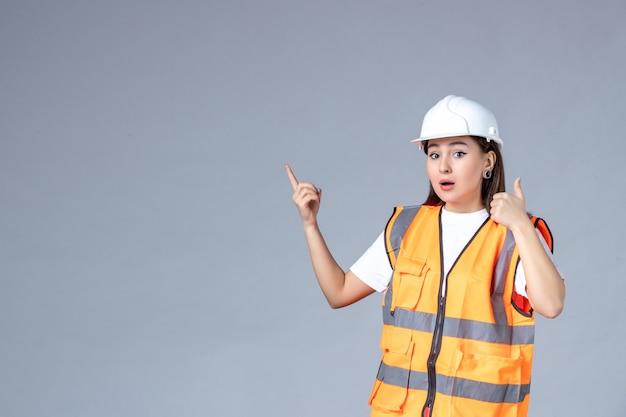 Vue de face du constructeur féminin en uniforme sur mur blanc