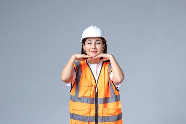 Vue de face du constructeur féminin en uniforme sur un mur gris