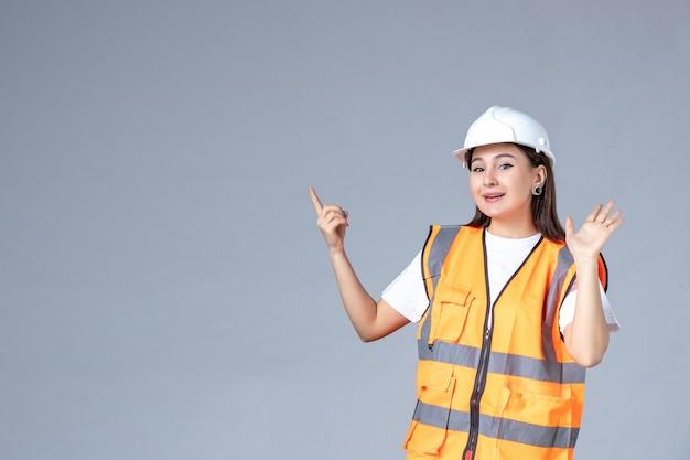 Vue de face du constructeur féminin en uniforme souriant sur mur blanc
