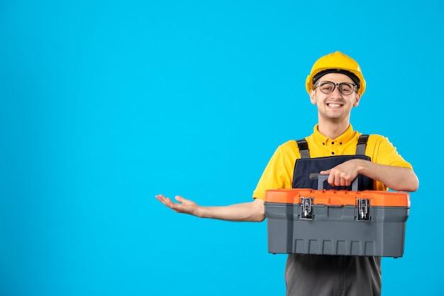Vue de face du constructeur masculin heureux en uniforme et casque avec boîte à outils sur mur bleu