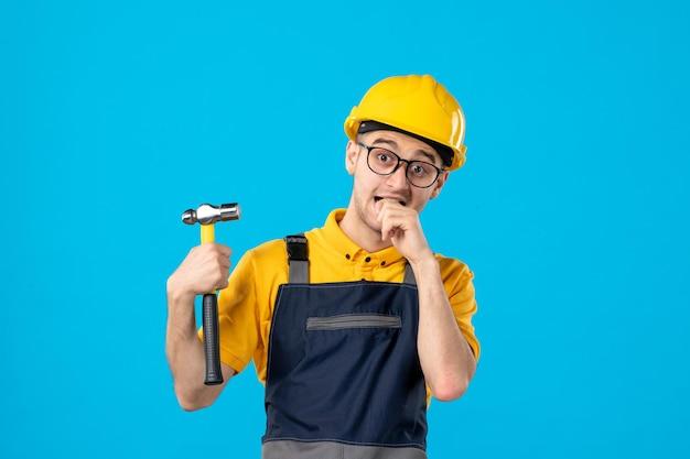 Vue de face du constructeur masculin nerveux en uniforme avec marteau sur bleu