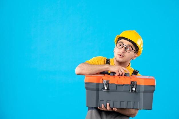 Vue de face du constructeur masculin en uniforme avec boîte à outils dans ses mains sur le mur bleu