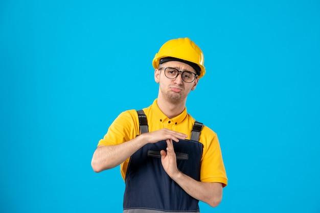 Vue de face du constructeur masculin en uniforme et casque montrant le signe t sur la surface bleue
