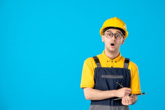 Vue de face du constructeur masculin en uniforme et casque en prenant des notes sur le mur bleu