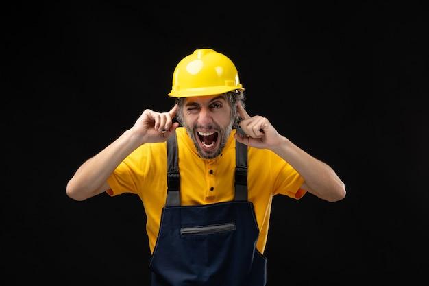 Vue de face du constructeur masculin en uniforme collant ses oreilles sur un mur noir