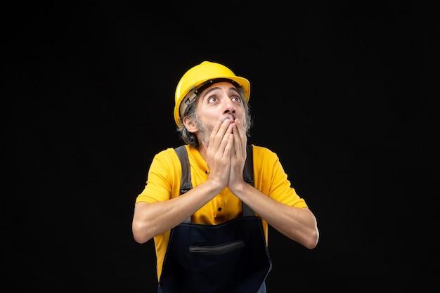 Vue de face du constructeur masculin en uniforme jaune sur le mur noir