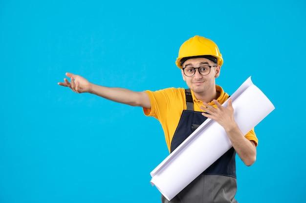 Vue de face du constructeur masculin en uniforme jaune avec plan sur bleu
