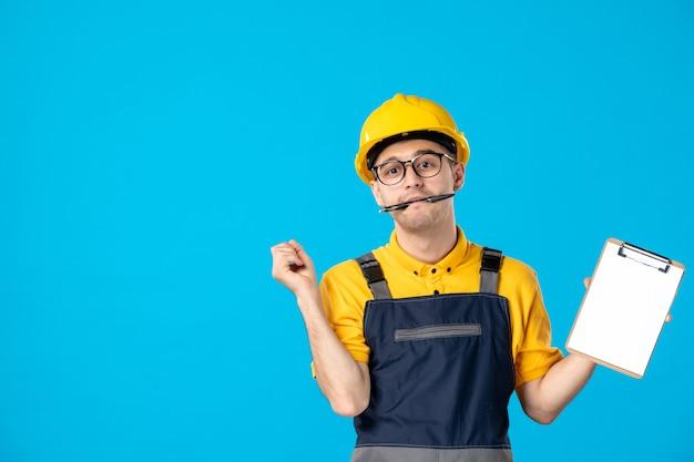 Vue de face du constructeur masculin en uniforme avec note de fichier dans ses mains sur le mur bleu