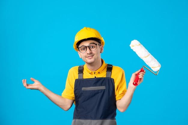 Vue de face du constructeur masculin en uniforme avec rouleau à peinture dans ses mains sur le mur bleu