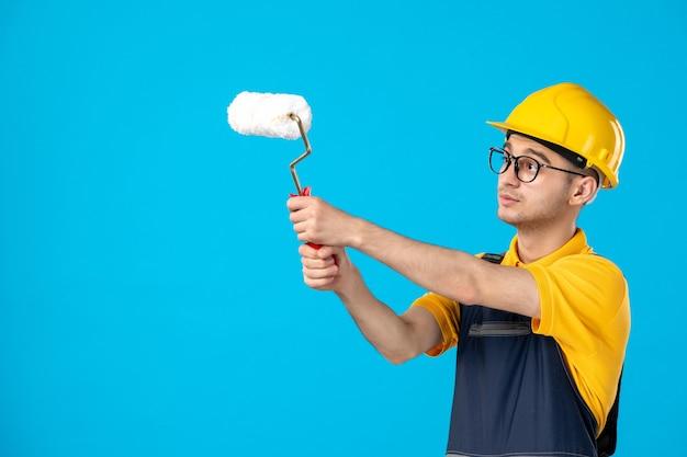 Vue de face du constructeur masculin en uniforme avec rouleau à peinture dans ses mains sur la surface bleue
