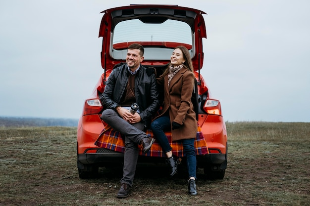 Vue de face du couple assis dans le coffre de la voiture