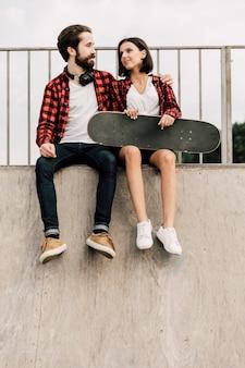 Vue de face du couple assis sur une rampe