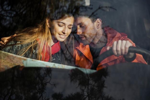 Vue de face du couple avec carte à l'intérieur de la voiture partant ensemble pour un road trip