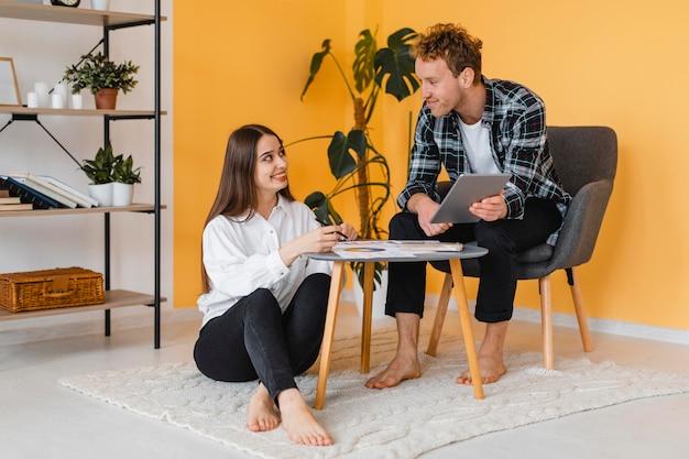 Vue de face du couple faisant des plans ensemble pour redécorer la maison