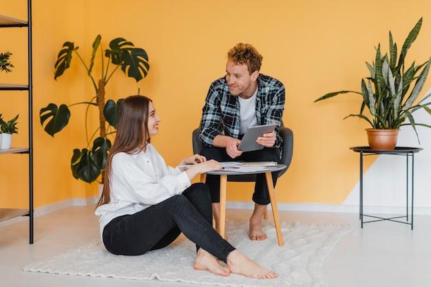 Vue de face du couple faisant des plans ensemble pour redécorer le ménage