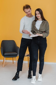 Vue de face du couple faisant des plans pour reconditionner la maison ensemble