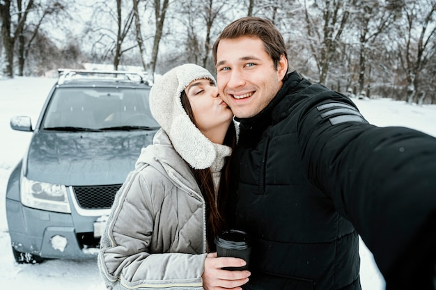 Vue de face du couple heureux prenant selfie lors d'un voyage sur la route