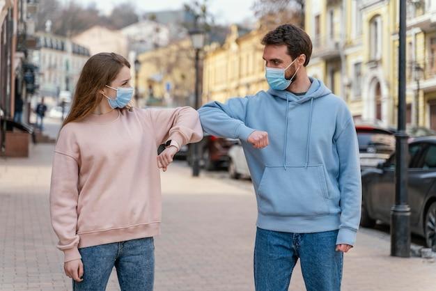 Vue de face du couple avec masque médical à l'aide du salut du coude