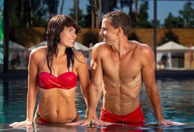 Vue de face du couple à la piscine