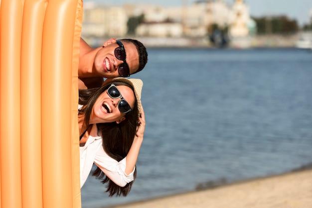 Vue de face du couple à la plage posant avec matelas pneumatique