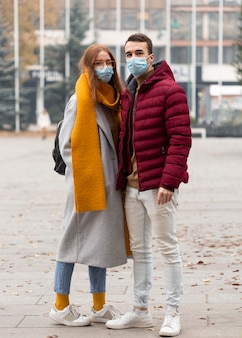 Vue de face du couple portant des masques médicaux